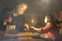 Painting depicting Joseph, carpenter and wood worker, chiseling by candlelight with his son Jesus looking on.