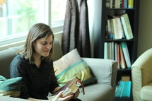 a woman holding a Bible while sitting on a couch