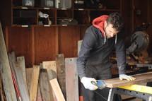 a man sanding wood in his workshop
