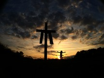 silhouette of a cross with a shroud and girl with open arms