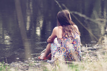 a woman sitting by the edge of a pond