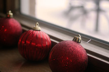 Red Christmas balls sitting on a windowsill.