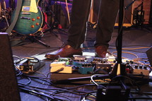 man's feet on guitar pedals