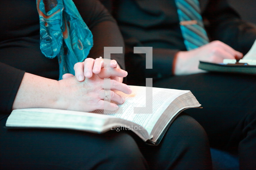 Bible on the laps of a couple during church