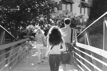 People walking across a bridge.
