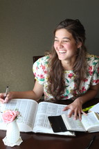 A laughing girl studying the Bible.