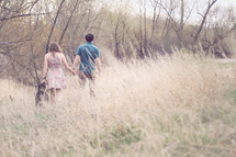 a couple walking holding hands through a field of tall grass
