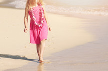 girl child wearing a Leis on a beach