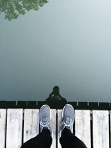 reflection of a man standing on a dock in lake water