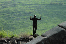 Silhouette of a man in praise and worship on a rock overlooking the ocean.
