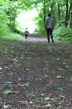 father and son walking on a path in the woods