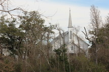 Church with a steeple through the trees.