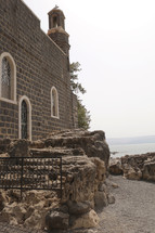 stone church with bell tower along a shore