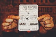 Hands holding a artistic prayer card.
