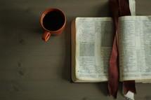 an open Bible and coffee mug on a coffee table