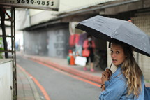 a woman with an umbrella walking down the street