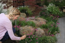 a woman with braided hair picking flowers in a backyard