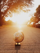 Sun shining on a globe in the middle of a street.