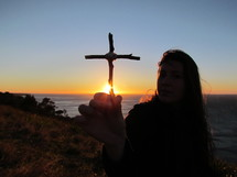 teen girl holding a cross made out of sticks