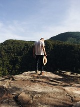 man standing on a rock holding a hat