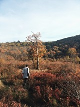 man walking up hill on a fall mountaintop
