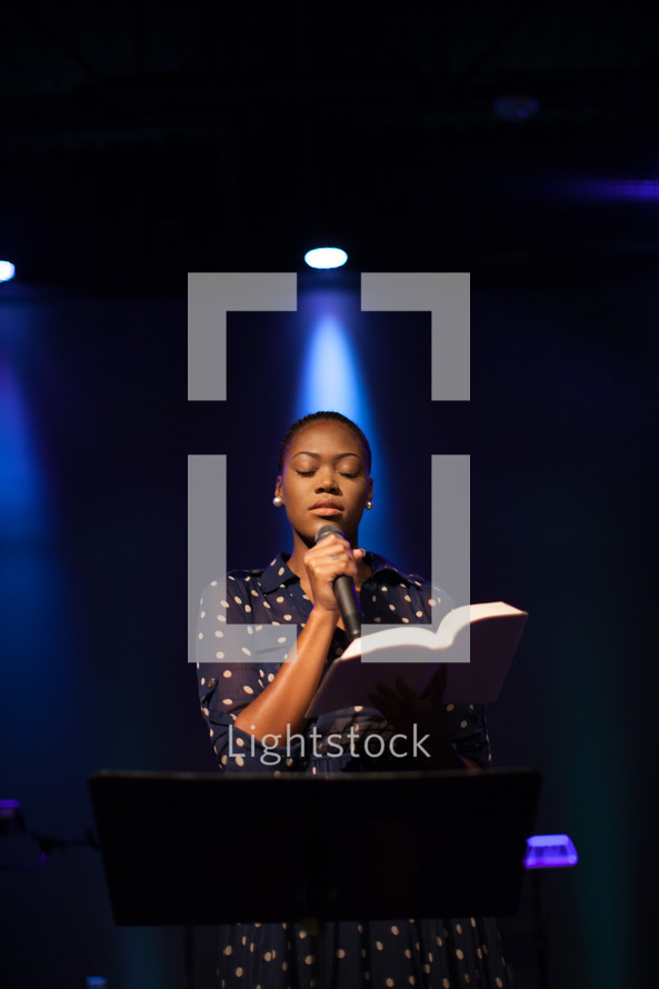 A woman on stage leading a worship service