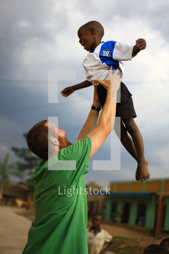 man holding boy in the air making a cross