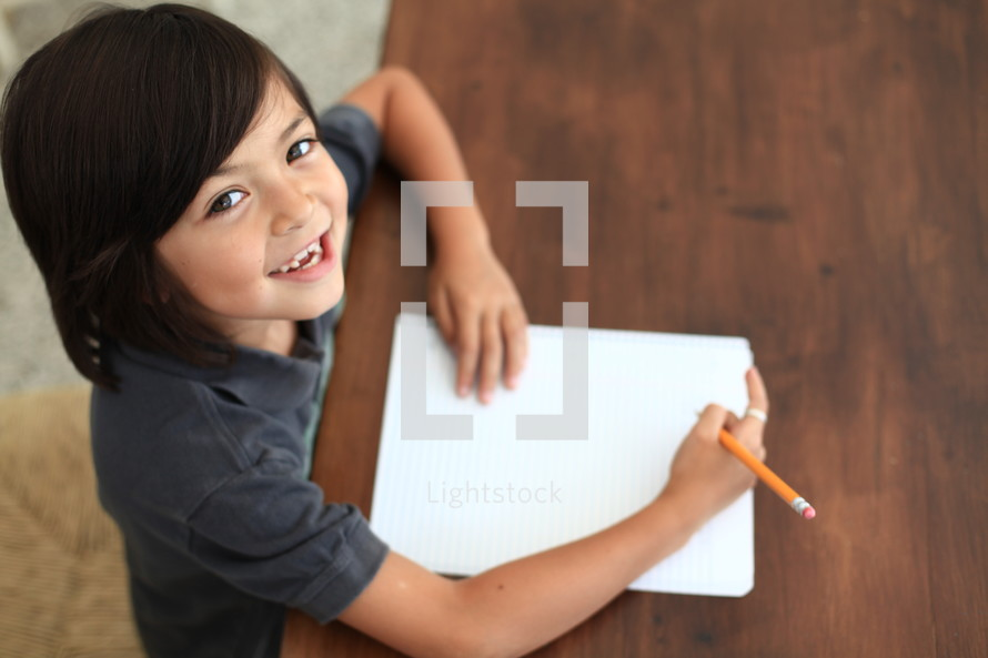 child with a smile writing on paper