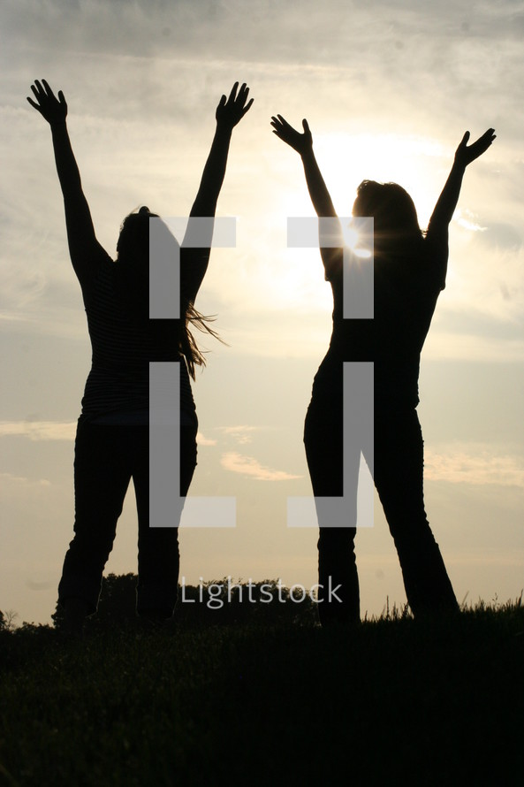 Women with hands raised outdoors