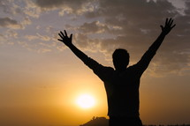 Silhouette of a man with raised hands at sunset / sunrise