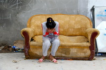 A young girl crying into her hands sitting on an old couch in a refugee camp in Northern Iraq