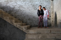 Two girls standing on concrete stairs in an abandoned building site. Now home to Azizi refugees in Kurdistan, Iraq
