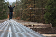 man standing on tracks with his arms raised in worship