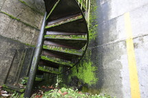 Outside winding staircase covered in moss