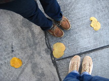 Fall leaves and shoes on a sidewalk