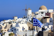 Flag of Greece flying in front of hillside village of homes.