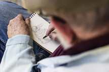 elderly man sketching a drawing on paper