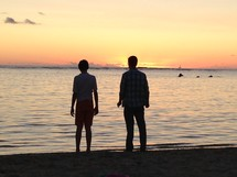 silhouette of a man and teenage boy looking out at the ocean