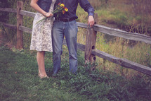 a couple standing by a fence outdoors in the country