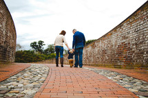 a family walking on a brick sidewalk holding hands