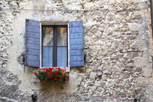 A window box, shutters, and window in a strong stone wall
