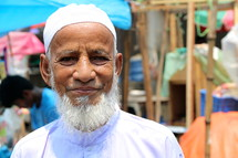 Elderly Muslim man with skull cap and grey beard