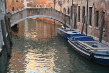 Bridge over moat with boats in the water.