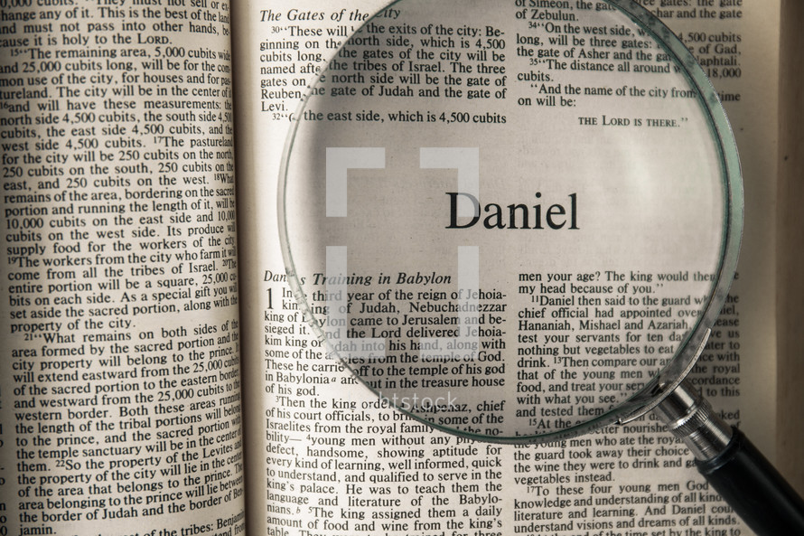 magnifying glass over Bible - Daniel