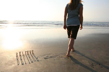 BELIEVE on sand and woman walking