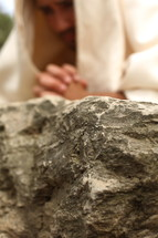 Jesus in prayer to God on a rock