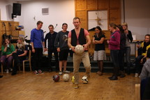 young adults in a choir room with soccer balls