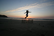 woman jumping over the word BELIEVE on a beach