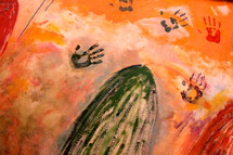 Mural with painted hand prints on orange color background