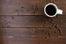 Coffee beans and a cup of coffee on a wooden surface.